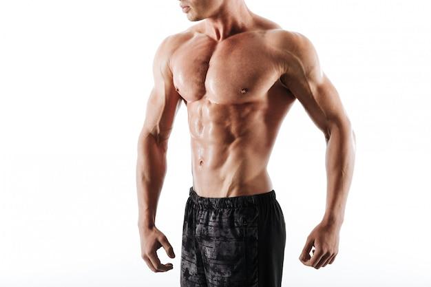 Foto recortada de hombre atlético sudoroso en shorts negros descansando después del entrenamiento
