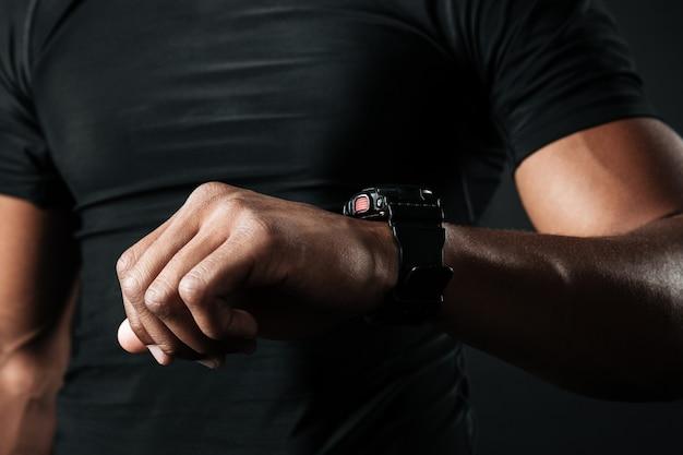 Foto recortada del hombre musculoso afroamericano comprobando el tiempo