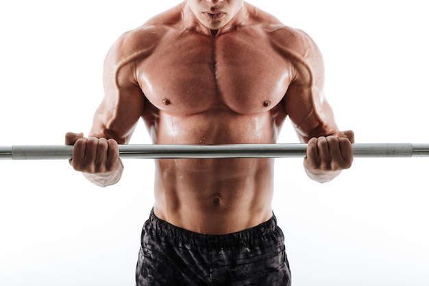 Foto recortada de hombre musculoso deportivo sudoroso en shorts negros haciendo ejercicio con barra