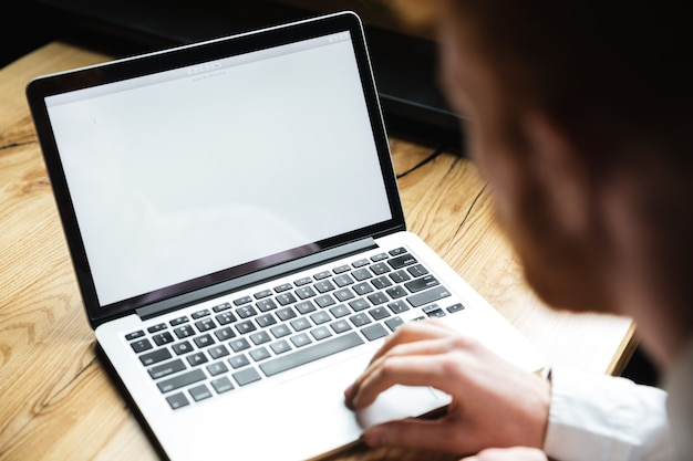 Foto recortada de joven usando laptop en mesa de madera