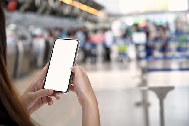 Foto recortada de la mano femenina que sostiene el teléfono móvil en la terminal del aeropuerto