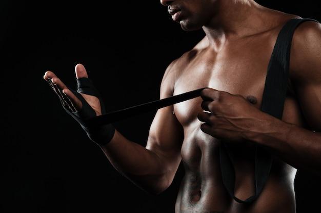 Foto recortada de manos joven boxeador afroamericano, vientos vendas de boxeo