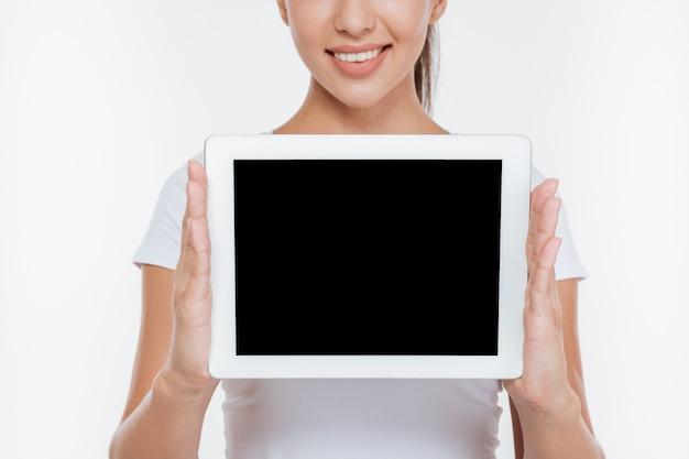 Foto recortada de mujer alegre sosteniendo tableta digital y mostrando la pantalla al frente aislado en la pared blanca
