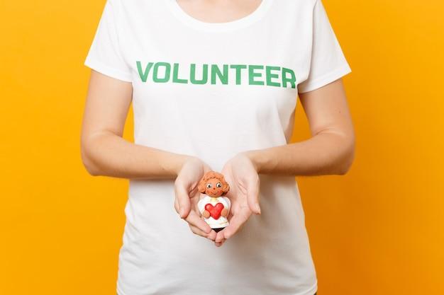 Foto recortada de mujer en camiseta blanca con inscripción escrita título verde voluntario sostén a angelito en palmas aisladas sobre fondo amarillo. ayuda de asistencia gratuita voluntaria, concepto de trabajo de gracia de caridad.