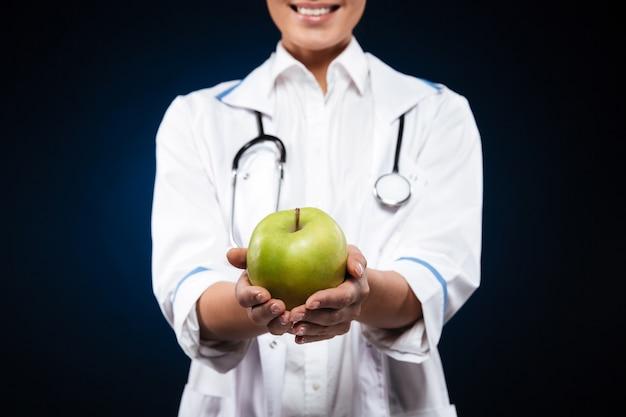 Foto recortada de mujer joven en bata médica con manzana verde