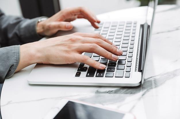 Foto recortada de una mujer joven estudiante de negocios sentada en un café en el interior con coworking de computadora portátil.