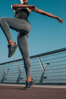 Foto recortada de una mujer levantando una pierna y estirando los brazos