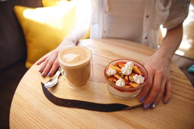 Foto recortada de pelirroja jovencita sentada en la cafetería