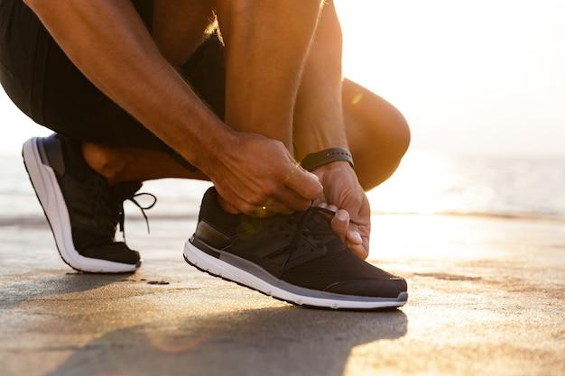 Foto recortada de piernas de hombre caucásico deportivo en chándal y zapatillas de deporte en cuclillas en el muelle junto al mar y atarse los cordones de los zapatos