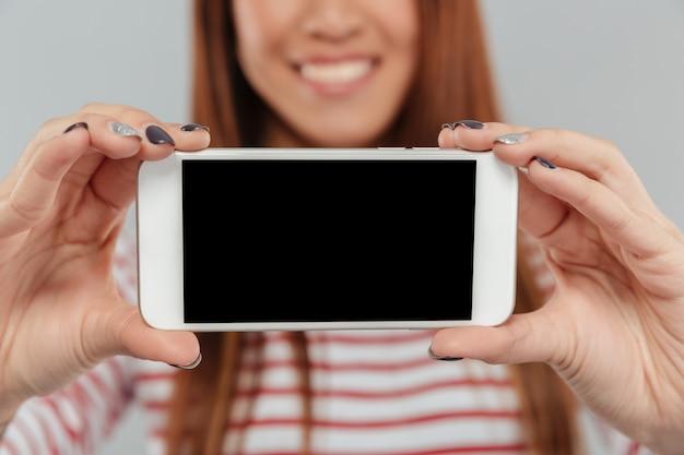 Foto recortada de sonriente mujer asiática mostrando la pantalla del teléfono