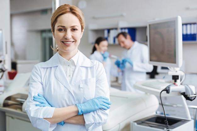 Foto de retrato. asistente de laboratorio joven positivo cruzando los brazos sobre el pecho y manteniendo la sonrisa en la cara mientras se ve exitoso