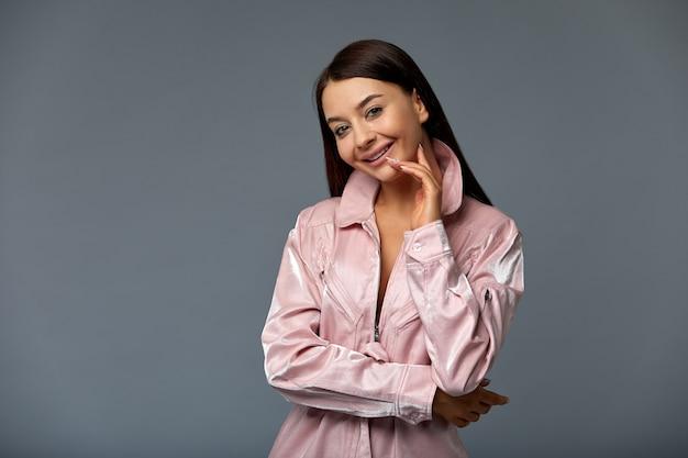 Foto retrato de una chica linda mujer con cabello oscuro en ropa rosa.