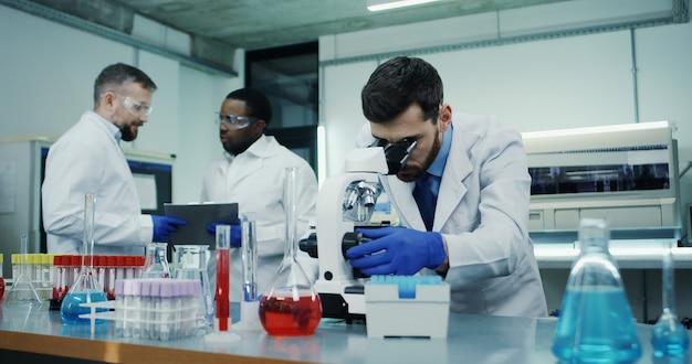 Foto de retrato del científico hombre caucásico mirando al microscopio mientras investigaba algo en el laboratorio, mientras sus compañeros de raza mixta hablaban en la escena.