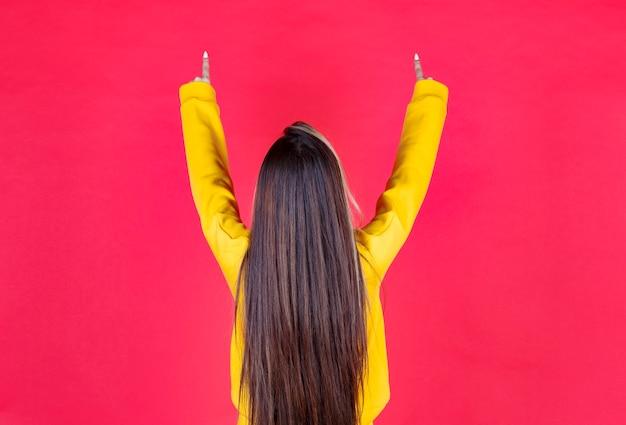 Foto de retrato de una hermosa niña modelo de pie y apuntando hacia arriba