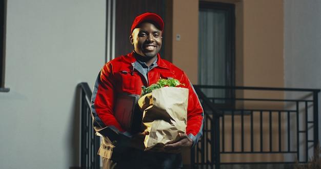 Foto de retrato del joven afroamericano del servicio de entrega de supermercado en el traje rojo y gorra con verduras frescas en el paquete de cartón