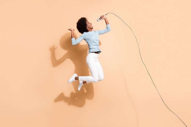 Foto retrato de mujer afroamericana emocionada cantando sosteniendo el micrófono en una mano en el aire aislado sobre fondo de color beige pastel