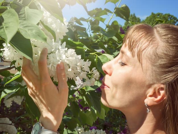 Foto de retrato de mujer feliz inhala el aroma de la lila blanca en primavera