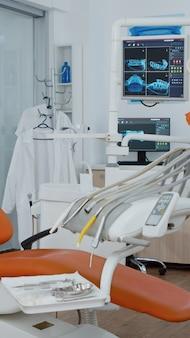 Foto reveladora de la silla de ortodoncia con nadie en las imágenes de rayos x de los dientes en la pantalla moderna