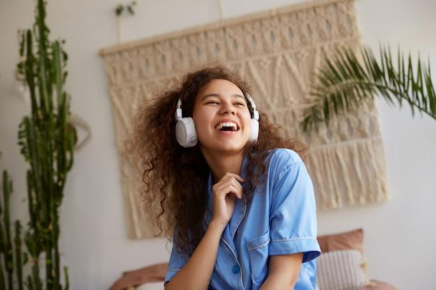 Foto de risa rizada joven agradable afroamericana, escuchando música favorita en auriculares, mira hacia otro lado y canta una canción.