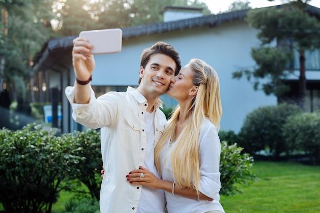 Foto romántica. agradable mujer feliz dando un beso a su novio mientras se toma un selfie con él
