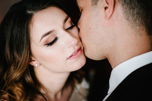 Foto romántica. el hombre abraza amorosamente a una tierna mujer. joven pareja de enamorados en el día de san valentín. de cerca.