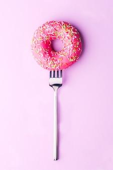 Foto de rosquilla rosa en horquilla en fondo vacío