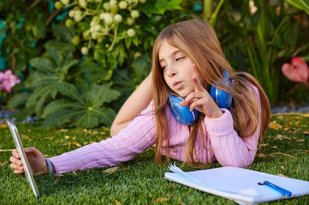 Foto rubia del selfie de la muchacha del niño con pc de la tableta en hierba