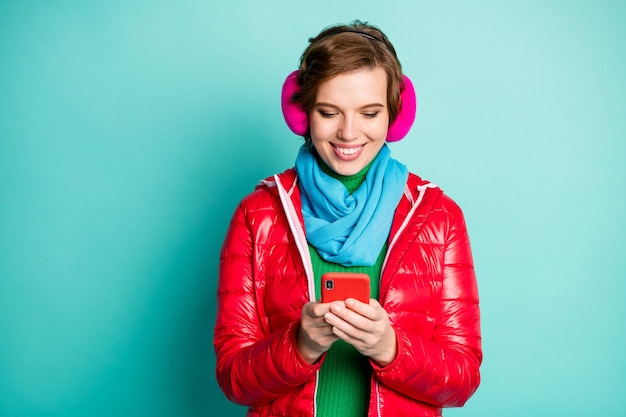 Foto de señora bastante divertida charlando teléfono escribiendo amigos que viajan al extranjero visten abrigo rojo casual bufanda rosa calentadores de orejas suéter aislado pared de color verde azulado