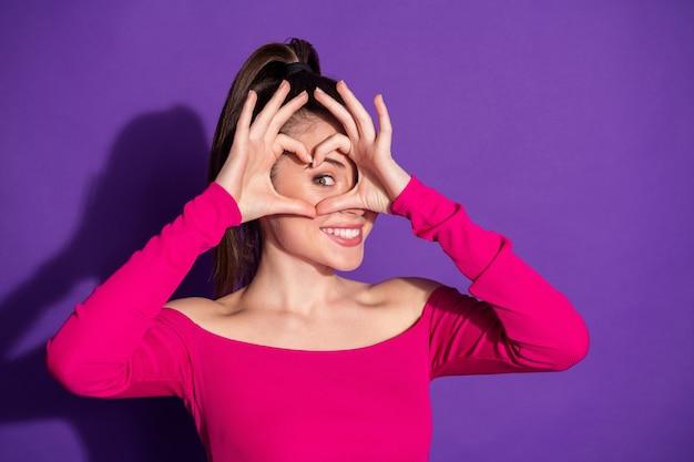 Foto de señora bonita con los dedos cruzados alrededor de los ojos en forma de corazón desgaste rosa hombros desnudos superior fondo de color violeta aislado