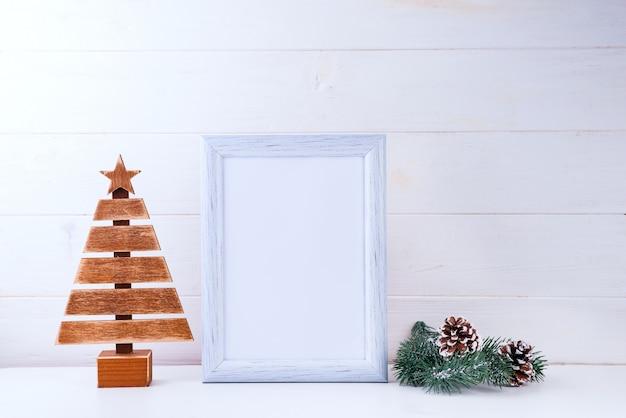 Foto simulada con marco blanco, árbol de madera y ramas de pino en madera blanca