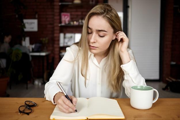 Foto sincera de una atractiva estudiante rubia en blusa blanca haciendo la tarea en el lugar de trabajo en casa, escribiendo en un cuaderno abierto, bebiendo té, con una expresión facial concentrada seria