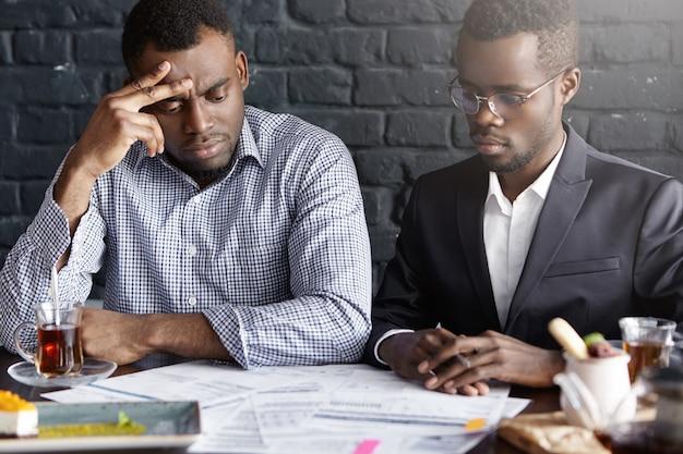 Foto sincera de dos apuestos socios comerciales afroamericanos con miradas frustradas