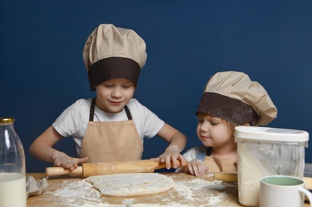 Foto sincera de la encantadora niña con gorro de cocinero mirando a su hermano mayor amasando masa para galletas o tarta