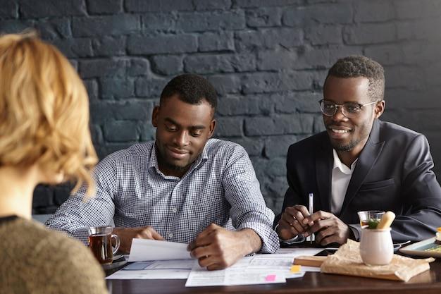Foto sincera del guapo gerente de reclutamiento afroamericano y su asistente