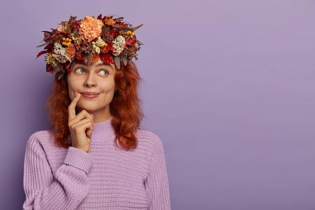 Foto sincera de una hermosa mujer pelirroja que tiene una expresión soñadora, mantiene el dedo cerca de los labios, está sumido en sus pensamientos, usa una corona de plantas