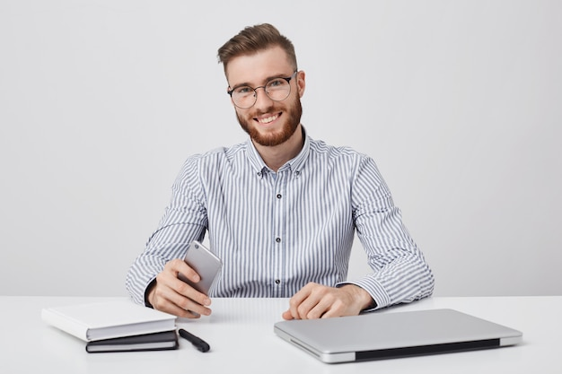 Foto sincera de hombre exitoso con barba espesa, utiliza tecnología moderna para el trabajo