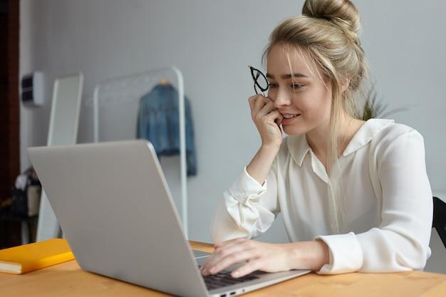 Foto sincera de una joven independiente positiva con peinado desordenado que usa un dispositivo portátil electrónico genérico en un escritorio de madera, trabajando de forma remota desde la oficina en casa, habiendo absorbido la mirada interesada