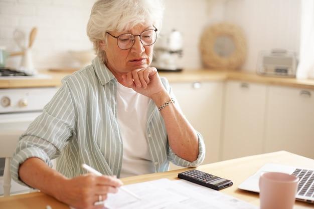 Foto sincera de una mujer caucásica jubilada seria con gafas calculando gastos, tratando de ahorrar dinero para compras costosas, pagando facturas domésticas en línea usando un aparato electrónico en la mesa de la cocina