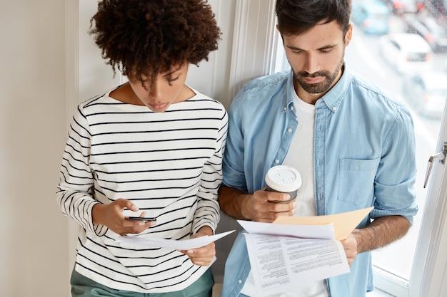 Foto de socios serios de raza mixta que discuten datos financieros