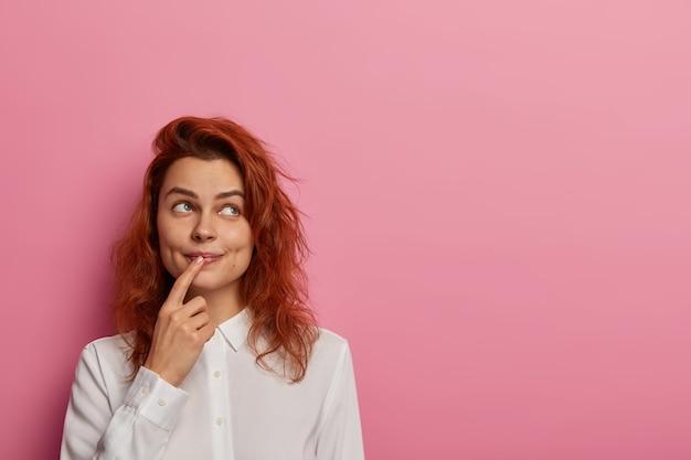 Foto de soñadora mujer pelirroja sueña despierta con algo, mira a un lado, mantiene el dedo índice en los labios, viste camisa blanca