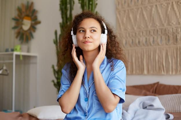 Foto de soñar con rizado joven agradable afroamericana, escuchando su canción favorita en auriculares, mira hacia otro lado con expresión feliz.