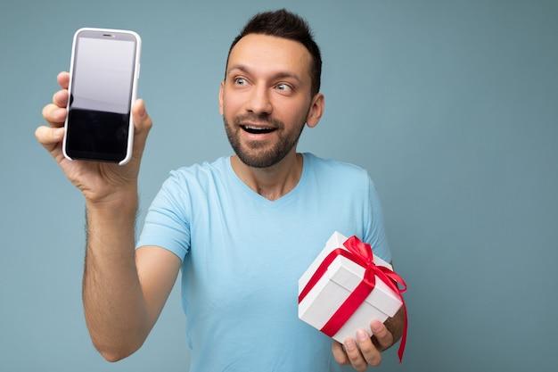 Foto de sonriente positivo apuesto joven brunet sin afeitar con barba vistiendo camiseta azul todos los días