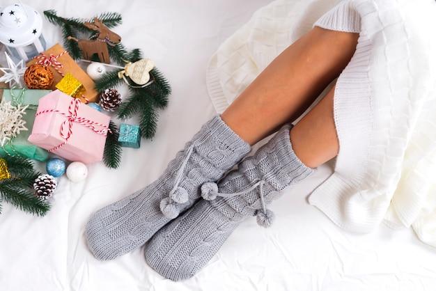 Foto suave de mujer en calcetines de punto con regalos de navidad, punto de vista superior