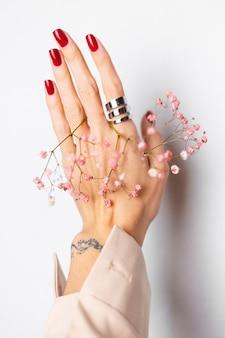 Foto suave suave de la mano de la mujer con gran anillo de manicura roja sostenga lindas flores secas rosa sobre blanco.