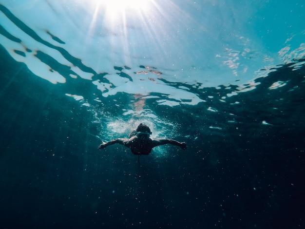 Foto submarina de mujer buceando en el mar