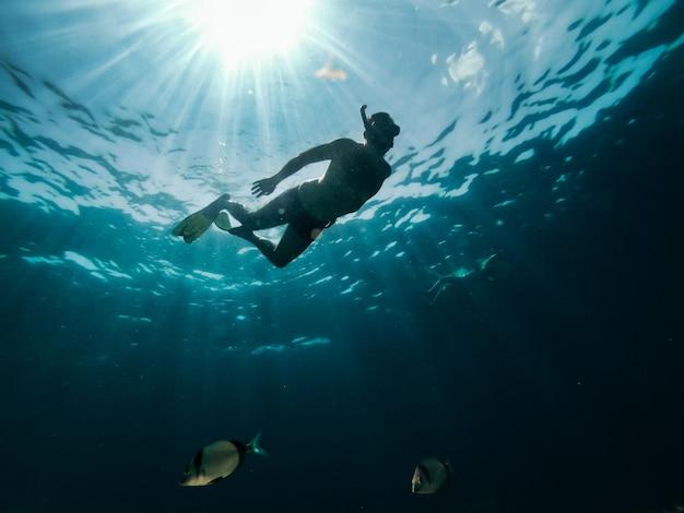 Foto submarina de pareja haciendo snorkel en el mar