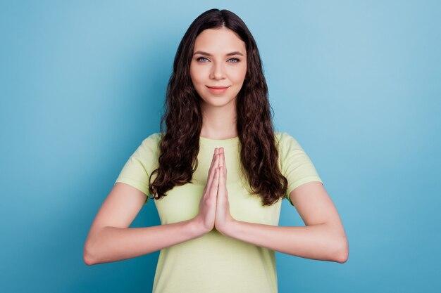 Foto de suplicar positivo bastante adorable niña mantenga las palmas juntas pedir favor sobre fondo azul.