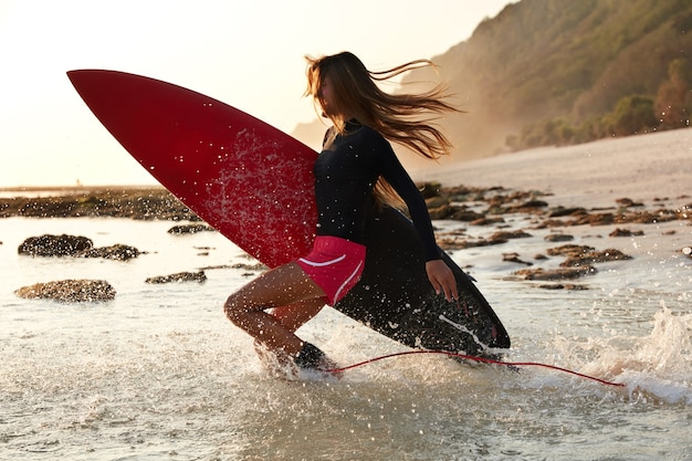 Foto de surfista activo salta al agua de felicidad, tiene tiempo para su pasatiempo favorito