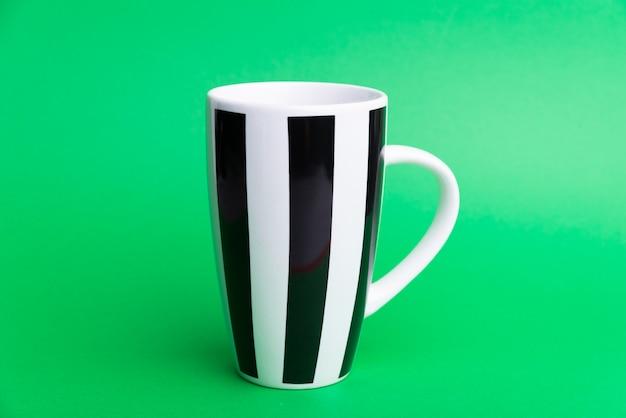 Foto de una taza blanca con líneas negras en verde aislado