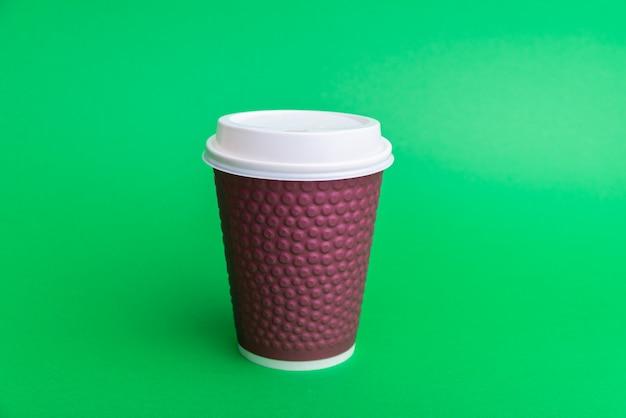 Foto de una taza para llevar púrpura con tapa de ehite en verde